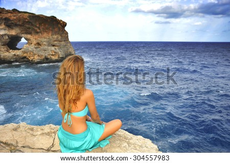 young attractive woman looking at sea horizon sitting alone on rock cliff in cyan glamour dress under a summer blue sky in relax , meditation and serenity concept - stock photo