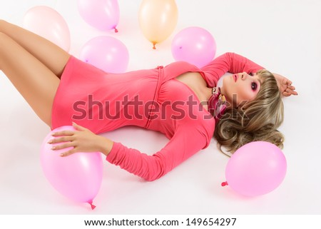 Young attractive woman lying down on white background with air balloons - stock photo