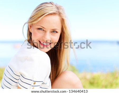 Young attractive woman near the ocean on a summer day - stock photo