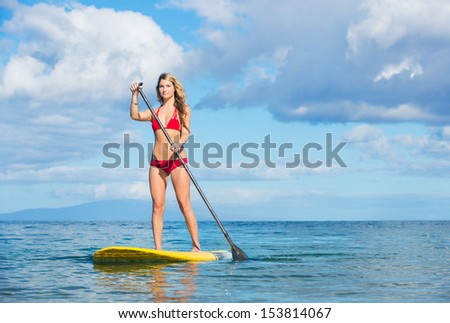 Young Attractive Woman on Stand Up Paddle Board, SUP, in the Blue Waters off Hawaii, Active Life Concept - stock photo