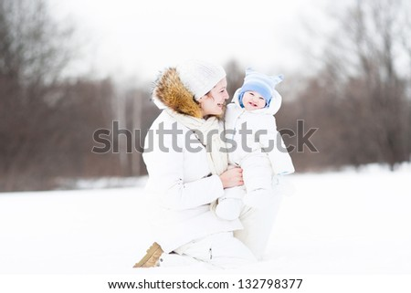 Young attractive woman playing with her baby in a snowy park - stock photo