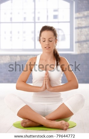 Young attractive woman practicing yoga, meditating in prayer pose in studio.? - stock photo