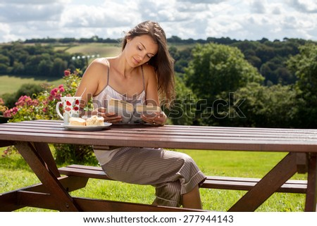 Young attractive woman, reading a book outdoor, enjoying coffee and sweet scones with jam - stock photo