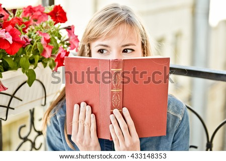 Young attractive woman reading a book outdoor sitting on the balcony - stock photo