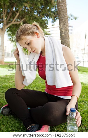 Young attractive woman relaxing from doing exercise in a park city, sitting down and drying her forehead sweat with a white towel during a sunny morning. - stock photo