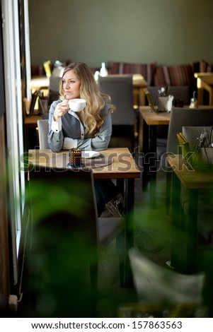 Young attractive woman sitting in cafe daydreaming over coffee - stock photo