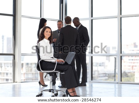 Young attractive woman sitting in office working with team in background - stock photo