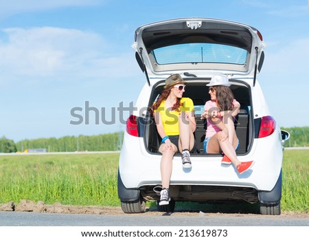 young attractive woman sitting in the open trunk of a new car, a summer road trip - stock photo