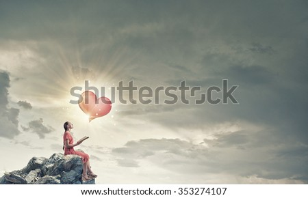 Young attractive woman sitting on rock top and reading book - stock photo
