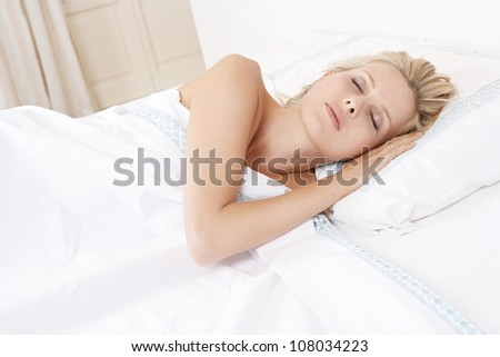 Young attractive woman sleeping in bed. - stock photo