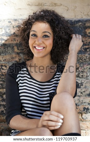 Young attractive woman smiling on urban background - stock photo