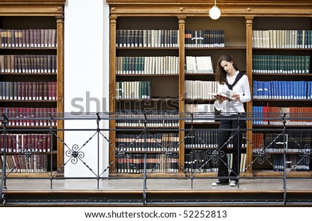 Young attractive woman standing in front of bookshelf in old university library reading a book. - stock photo