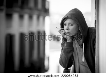 young attractive woman suffering depression and smoking in stress outdoors at home balcony terrace window in pain and grief feeling sad and desperate in urban background in black and white - stock photo