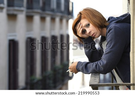 young attractive woman suffering depression and stress smoking outdoors at the balcony window in pain and grief feeling sad and desperate in urban background - stock photo
