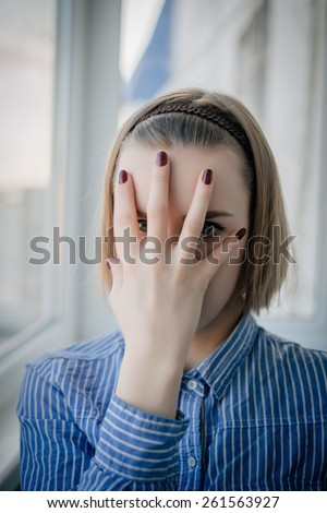 young attractive woman suffering depression and stress standing alone in pain and grief against window feeling sad and desperate at home with studio backlight - stock photo