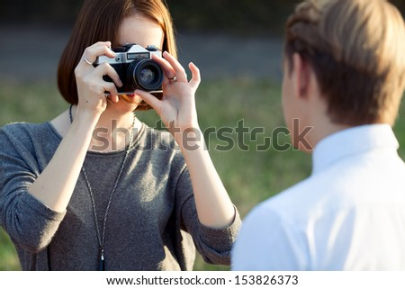 young attractive woman taking photos of her boyfriend in the park - stock photo