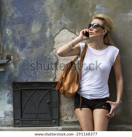 Young attractive woman talking on the phone standing on the street of the old town. - stock photo