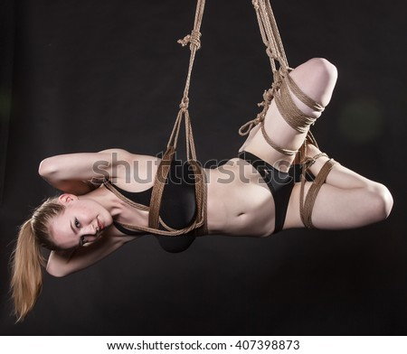 Young attractive woman tied with a rope. BDSM - stock photo