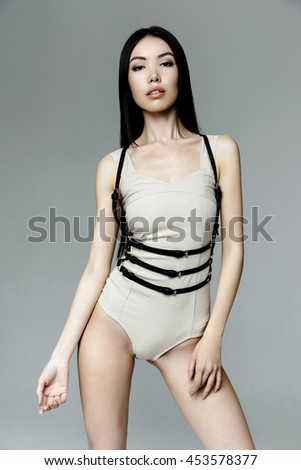 Young attractive woman wearing gray kombidress with leather black belt on white background - stock photo