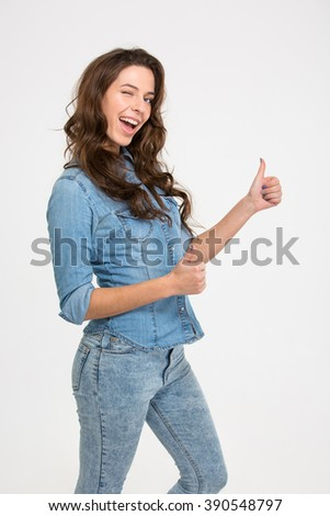 Young attractive woman winking and showing thumb up isolated on a white background - stock photo
