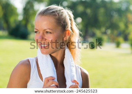 young attractive woman with a white towel around his neck, resting after sport exercises - stock photo