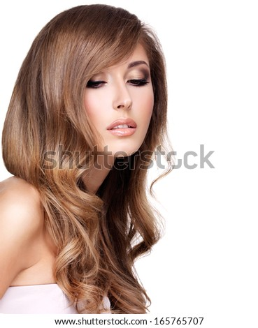 Young attractive woman with beautiful long wavy hair posing at studio. Isolated on white - stock photo
