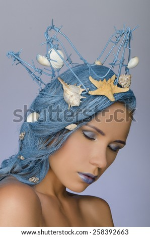 young attractive woman with blue hair, crown and shells - stock photo