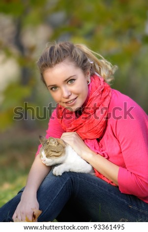 young attractive woman with cat outdoors - stock photo