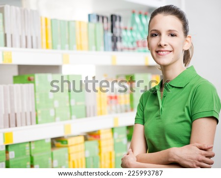 Young attractive woman with crossed arms at supermarket standing against shelves. - stock photo