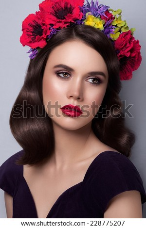 Young attractive woman with curly hairstyle, flowers in her hair and beauty make-up, looking away - stock photo
