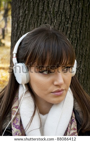 Young attractive woman with headphones listening music in park at fall outdoors - stock photo