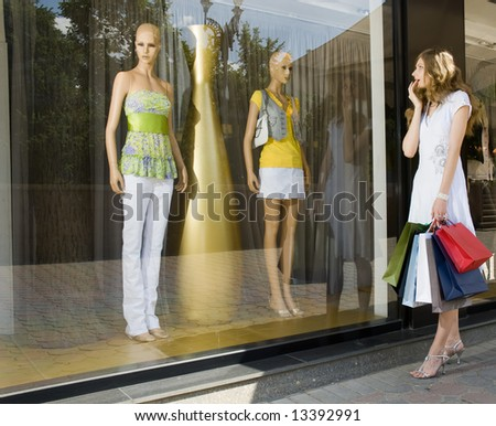 Young attractive woman with paper bags looking at a shop window - stock photo