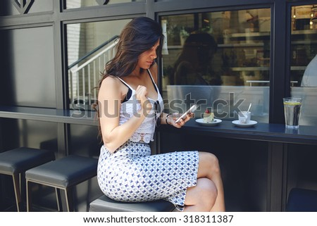 Young attractive woman with perfect figure and large breasts sitting at the coffee shop table and breakfast with sweet dessert and cup of cafe, Latin female reading text  message on her mobile phone - stock photo
