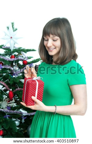 young  attractive woman with  red gift near christmas tree. isolated on white background - stock photo