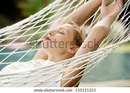 Young attractive woman with red lipstick laying down on a white hammock in a garden, while on vacations. - stock photo