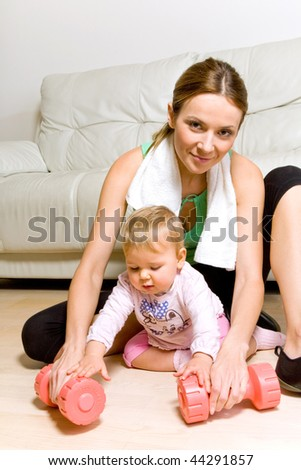 Young attractive woman with with her baby girl exercising with dumbbells - stock photo