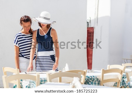 Young, attractive women choosing a place for seat in outdoors restaurant - stock photo