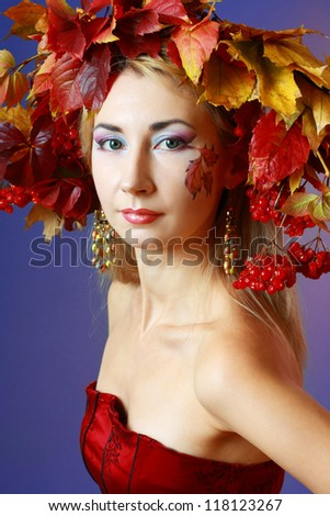 Young Autumn Woman. Beautiful makeup and hat from autumn yellow and red leaves and gold dress - stock photo
