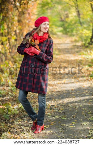 Young autumn woman in autumn park - stock photo
