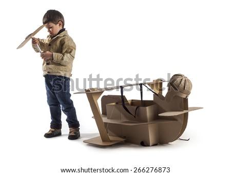 Young aviator assembles cardboard plane. Making airscrew. - stock photo