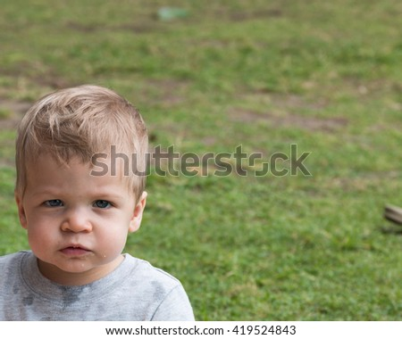 Young baby boy close up on face in a green field - stock photo