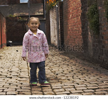 Young baby girl playing on cobble stoned alley - stock photo