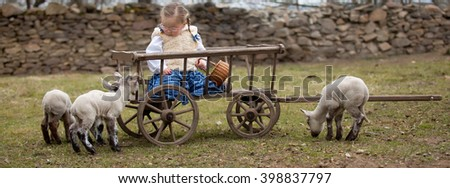 Young baby girl sitting on wooden carriage with lambs - stock photo