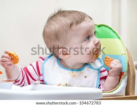young baby learning how to feed herself. - stock photo