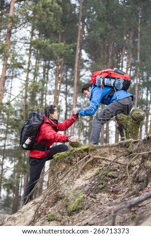 Young backpacker assisting friend while hiking in forest - stock photo