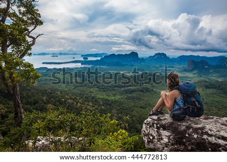 Young backpacker sitting on a cliff and looking to a valley - stock photo