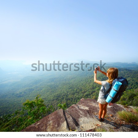 Young backpacker standing on top of a mountain and taking a picture of a morning valley - stock photo