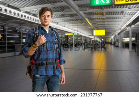Young backpacker with a backpack in an international airport on his way to the gate - stock photo