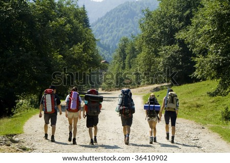 Young backpackers walking in the mountains in a summer day - stock photo