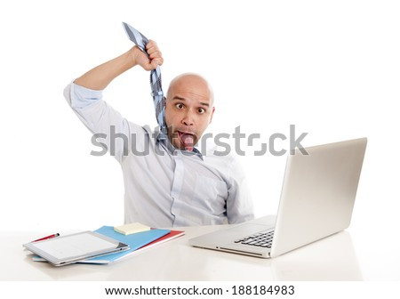 young bald south american business man choking himself with his own tie in desperation while being in stress , overworked and frustrated while working with computer at office desk - stock photo